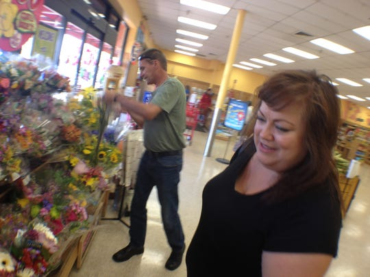 Todd Woodruff and Gina Greisen, president of Nevada Voters for Animals, pick out bouquets of flowers at a Trader Joe's store in Las Vegas. Woodruff bought the flowers to leave at a Walmart and a Cici's pizza restaurant where his daughter, Amanda Miller, and her husband, Jerad Miller, killed two police officers and a bystander on June 8. Woodruff also planned to leave flowers for his daughter, who killed herself during a standoff with police that day at the Walmart. Greisen led a crowd-funding effort to save the Millers' two cats and get them back to Woodruff's family in Lafayette.