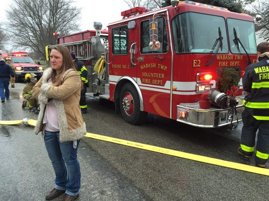 Candace True watches Wednesday from the 300 block of Vicksburg Lane as firefighters check for traces of the fire that left her, her husband, Billy True, and their three daughters homeless eight days before Christmas. The family has found temporary housing and has been thankful for all of the offers to help, Candace True said.