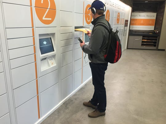 Justin Sinclair, a senior studying accounting at Purdue University, picks up a package at Amazon's first brick-and-mortar store in Krach Leadership Center.