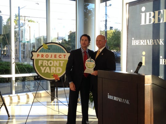 Ben Berthelot, left, director of the Lafayette Convention and Visitors Commission, accepted a Mayor-President's Front Yard Award from Joey Durel.