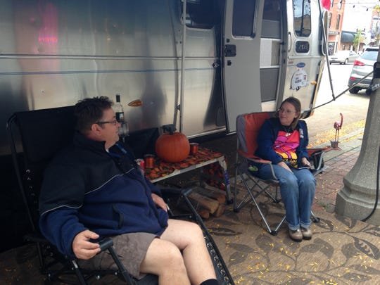 """Dan and Dawn Bihary of Ohio sit and chat by their Airstream trailer parked on Main Street in downtown Eaton Rapids on Oct. 2 during the first night of """"Urban Air."""""""