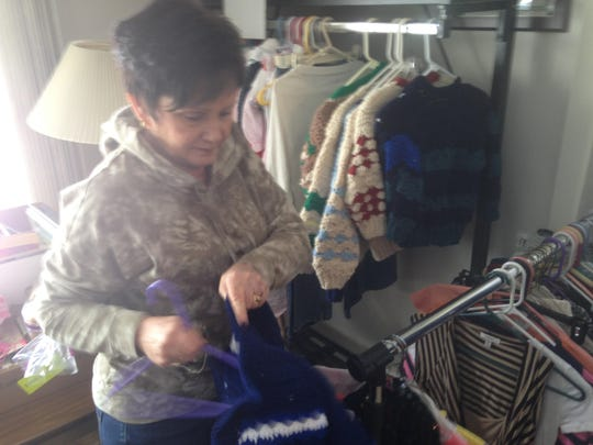 Linda Keep of Holt puts some of her mother's sweaters on hangers at the Our Savior Lutheran Food Bank in Lansing.
