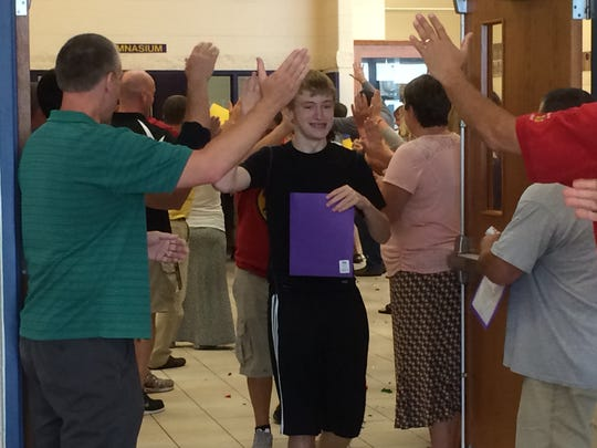 """Freshman Jacob Gomm is greeted with high fives from teachers as he walks through the """"welcome gauntlet"""" during Freshman Academy at Two Rivers High School. The program invites freshmen to the school a week early to meet their teachers and find their classrooms."""
