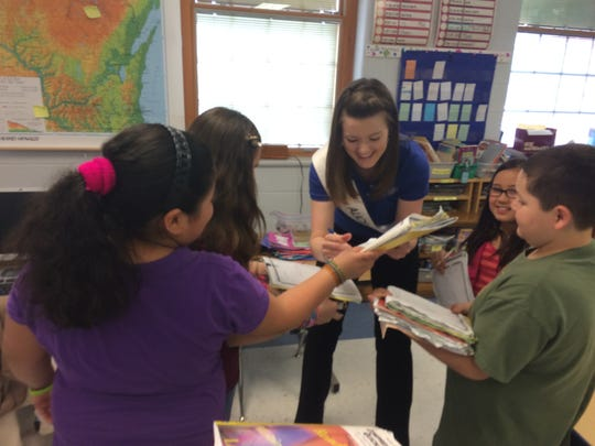 Wisconsin's 67th Alice in Dairyland, Zoey Brooks, autographs students' notebooks after giving a presentation on Wisconsin agriculture at Jefferson Elementary School in Manitowoc on March 25.