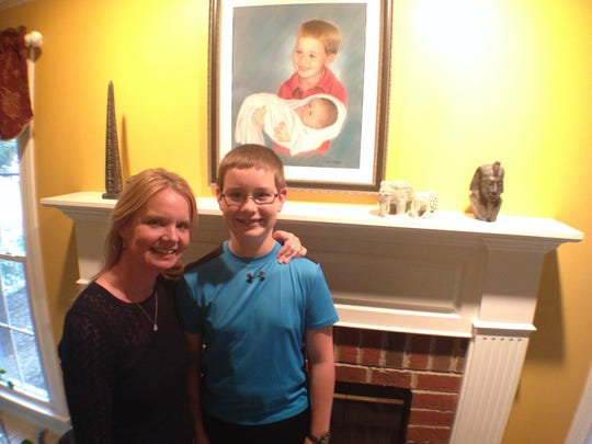 Kristi Hay and 13-year-old son, Callum, stand in front of the portrait of him and his infant sibling, Aiden, who died a few days after birth.