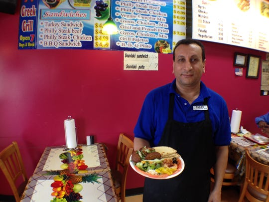 Magdi Ishak, owner of Opah Greek Cafe, holds a hummous platter. Opah Greek Cafe is located at 133 James Luscinski Drive beside the Old Fort Parkway Walmart.