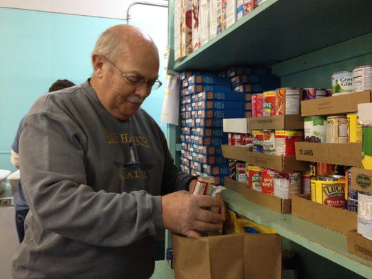 Jerry Gonyea, a volunteer with the United Ministries Food Bank of Robertson County, fills a food bag for a needy family on Thursday, Nov. 13.