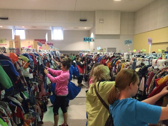 Shoppers search the racks during a recent Three Bags Full sale.