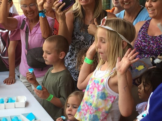 Sparrow Millard, 8, throws her hands up after finishing the Living Desert's Peep Eating Contest on Saturday.