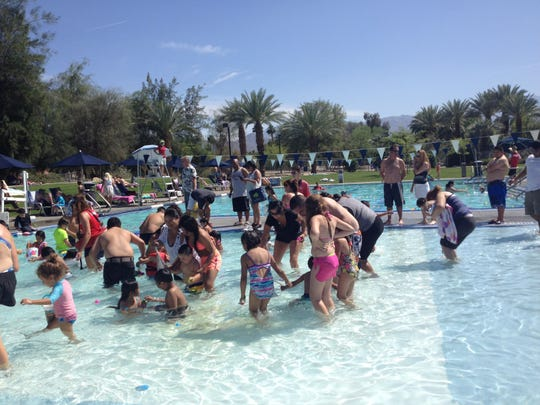 Children swim and search for Easter eggs at the annual underwater Easter egg hunt at the Palm Desert Aquatic Center Sunday afternoon.