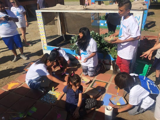 "Students painted tiles of the vegetable garden after completing the six kilometer walk during the ""Walking for Water"" event."