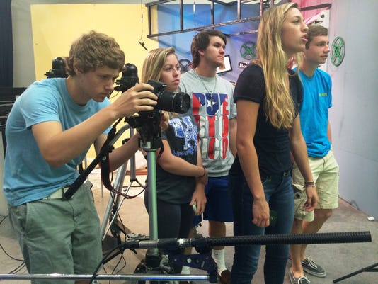 Eustis High School students film a TV show that airs on the local government access channel. Eustis High School students film a TV show that airs on the local government access channel. From left to right: Christian Rada, Emma Rodriguez, Lauren Levingston