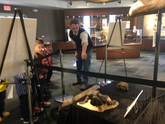Museum volunteer and paleontology student Phil Webster gives a guided tour to kindergarten and first grade students from Garfield Elementary School on a field trip to the Nasr Science Museum.