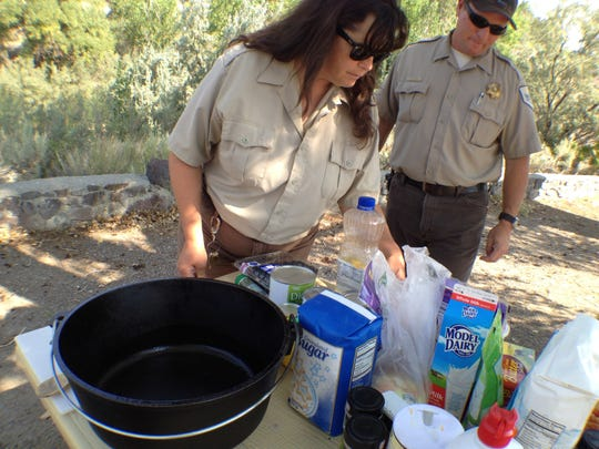Lahontan State Recreation Area seasonal worker Laura Vernon assembles ingredients for a dish she's going to make in a Dutch oven while park supervisor Tony Beauregard looks on.