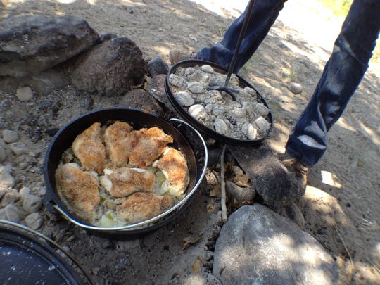 Lahontan State Recreation Area seasonal worker Tabitha Coughlin takes the lid off a chicken and rice dish cooked in a Dutch oven on Aug. 8.