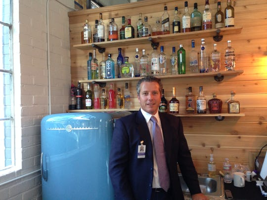 Lobbyist John Griffin beside his grandmother's old, remodeled refrigerator.