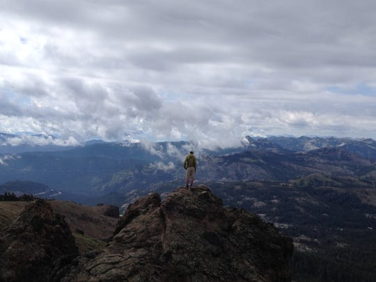 Ultralight hiking adventurer Justin Lichter takes in views of the Tahoe National Forest from a spot near Basin Peak near Truckee in July. Lichter and Shawn Forry, of Midpines, Calif., are attempting to through-hike the Pacific Crest Trail in winter.