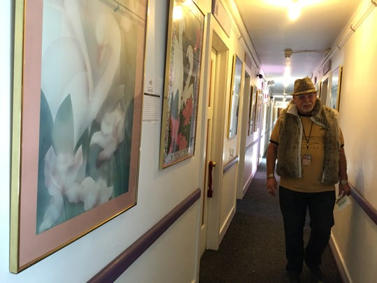 """""""Jungle"""" Jim Gibson, who owns the Morris Burner Hotel, walks past some of the swan prints that will be up for auction Saturday at the hotel. All proceeds will go toward helping to start an art program at the Reno/Sparks Gospel Mission."""