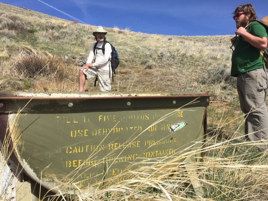 Kirk Peterson and Jake Kastner check out a rusted cattle trough while hiking Petersen Mountain on April 9, 2015.