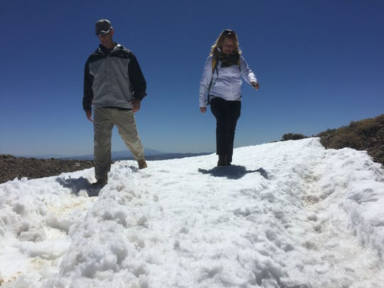 Lt. Col. Gregory K. Gibbons, commander of the Hawthorne Army Depot, and Kathy Trujillo, a fifth generation Hawthorne resident, negotiate a small snowfield near the top of Mt. Grant in Mineral County on April 17, 2015.