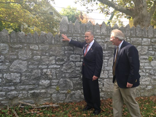 Sen. Charles Schumer, left, examines the original wall