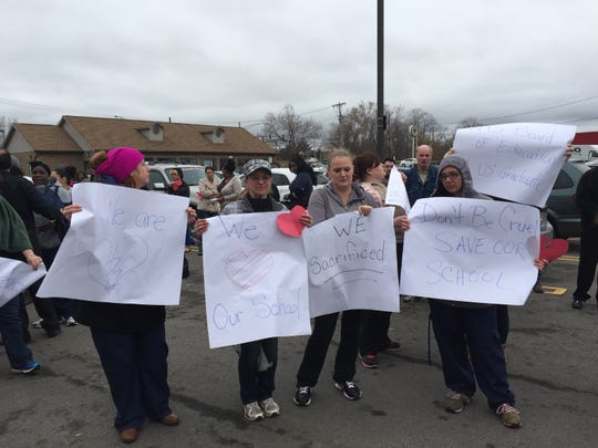 Students hold signs protesting the sudden closure of Everest Institute