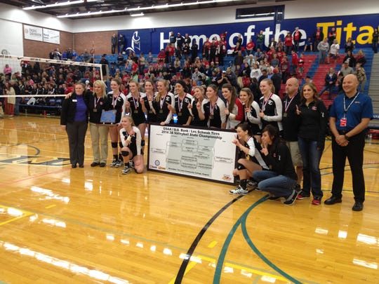 Santiam Christian's volleyball team poses with the 3A state championship trophy on Saturday, Nov. 8, 2014.
