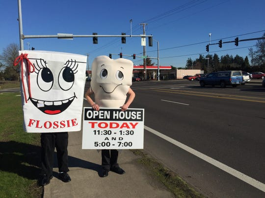 "Mascots ""Flossie"" and ""Molar Man"" invited drivers to stop by Oak Park's open house Friday."