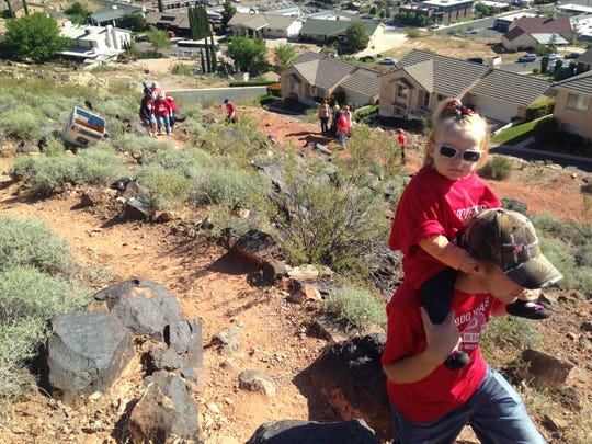 """People walk the narrow trail leading up to the iconic """"D"""" on the Black Hill on Saturday to help whitewash it as part of Dixie State University's celebration of the D's 100th anniversary."""
