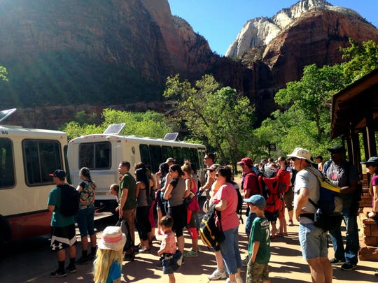Visitors gather to board the shuttle at Zion National Park.