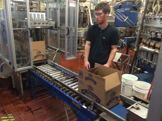An employee at the Stevens Point Brewery loads boxes