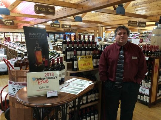 Jeff Tewes, Cellar 70 manager, stands next to a display