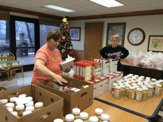 """Volunteers help sort food and toiletries that were donated by Dave Suchon, owner of Dave's Body Shop, on Dec. 15. The items were divided into 74 bags and distributed to residents of Hi-Rise Manor. """"The people here, they'll be so happy now,"""" said Sister Leone Juszczyk, who helps coordinate the drive. """"It's their Christmas present."""""""