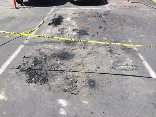 The charred asphalt where five vehicles caught fire at the Holiday Inn on July 16.