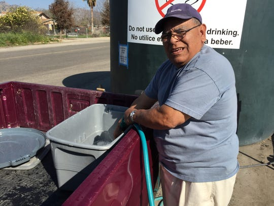 Felix Herrera of East Porterville fills containers in the back of his pickup truck with with water from a 5,000 tank, one of two in the town providing non-potable water — for washing clothes, showering and flushing toilets, but not for drinking. Herrera's home is one of nearly 600 in the town that have had their wells run dry due to the Valley's drought.