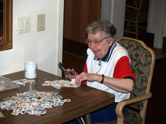Sister Benedicta Berger, SCSC, trimming stamps at Bell Tower Residence.