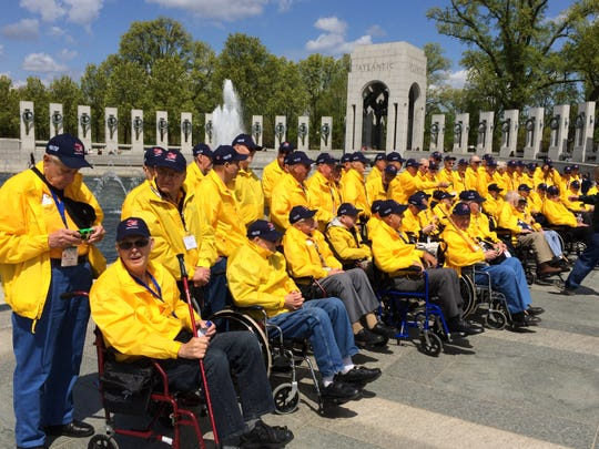 The 80 veterans on the Never Forgotten Honor Flight gather for a group photo at the World War II Memorial in Washington, D.C., on Monday during the Never Forgotten Honor Flight.