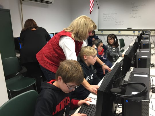 Instructional facilitator Andrea Edwards helps students in Deb Miller's fifth-grade class at Sloatsburg Elementary in the Ramapo Central School District participate in an hour of code during Computer Science Education Week.