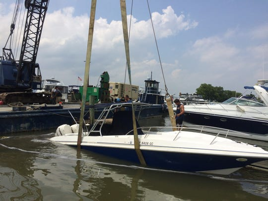 The Fountain is hoisted out of the water at the Tarrytown marina by a crane barge from Petersen Boat Yard and Marina in Clarkstown on July 3, 2014, after the Fountain sank. The Westchester County police marine unit responded and called for the crane barge. Responders also placed a boom and absorbent materials around the boat to contain its leaked fuel.  Police believe the vessel likely was damaged from winds and rough seas the night before that caused it to take on water.