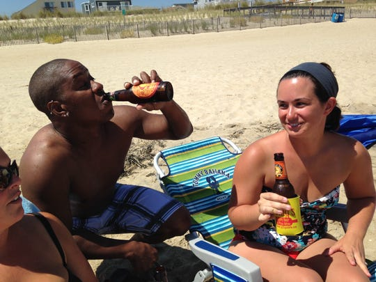 From left, Dana Diehl, Asher Conerly and Jessica Diehl relax with a beer in South Bethany, where alcohol is permitted.