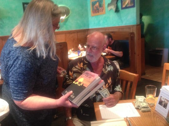 Author Shaun D. Mullen signs copies of his book for Phyllis McGuire Fantini at a book signing/reunion concert by Snakegrinder and the Shredded Field Mice.