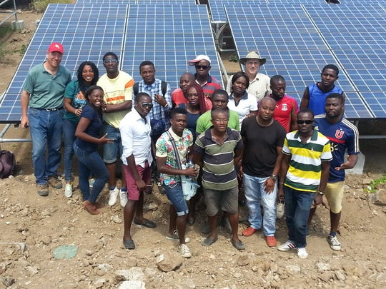 Residents of Annobón in Equatorial Guinea in Africa are photographed in front of new solar panels. Two Wilmington companies developed the panels.