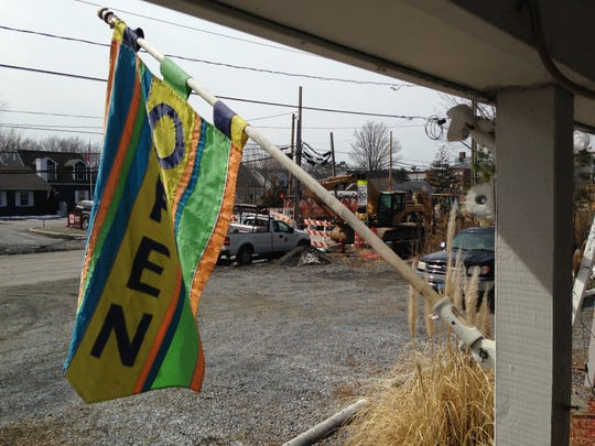 A flag beckons visitors into the Ellen Rice Gallery in Ocean View as construction on Del. 26 grinds on Monday in the background.