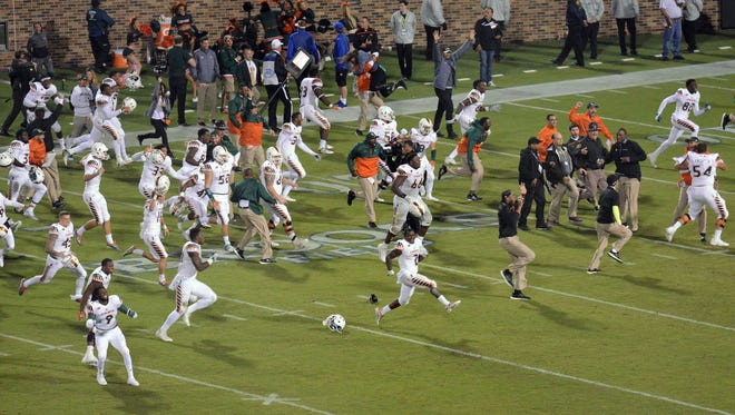 Miami players pour onto the field to celebrate their 30-27 win against Duke after scoring on an eight-lateral play in the final seconds.