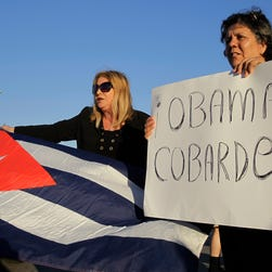 "Ana Lourdes Cuesta, left, and Liliana Cuerra in Miami on Dec. 17, 2014, protest the Obama administration's decision to re-establish diplomatic relationships with Cuba. Cuerra holds a sign that reads ""Obama coward."""