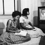 In this 1958 file photo, students Thelma Mothershed, left, and Melba Patillo watch a biology film on television as the Little Rock School Board and local TV stations began a supplemental educational series for students of the four high schools in Little Rock closed during the integration struggle.
