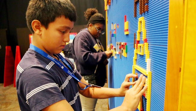 """Joel Madrigal, left, and Danea Harrison,  both seventh graders at University Prep Science & Math in Detroit are  playing with LEGOS  at the new interactive exhibit , """"Toyotopia"""" at the Michigan Science Center that focuses on learning through play. Photographed Thursday, Oct. 15, 2015."""