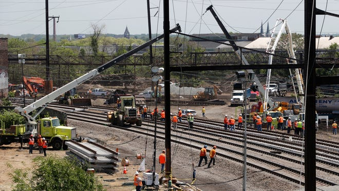 Workers labor on the site where a deadly train derailment happened earlier in the week, Friday, May 15, 2015, in Philadelphia. Amtrak is working to restore Northeast Corridor rail service between New York City and Philadelphia. Service was suspended after a train derailed in Philadelphia on Tuesday night, killing eight passengers and injuring more than 200. (AP Photo/Julio Cortez)