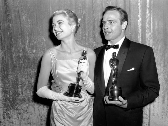 Oscar winners Grace Kelly and Marlon Brando pose with