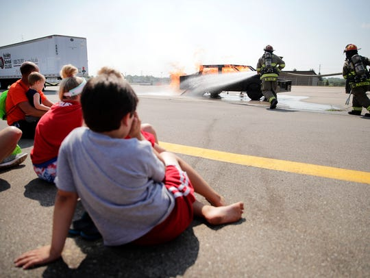 Children watch as firefighters Nick Seelow and Lisa